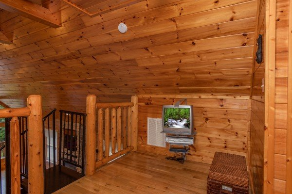 A spiral staircase leads to the loft with a tv and seating area at Can't Bear to Leave, a 1-bedroom cabin rental located in Gatlinburg