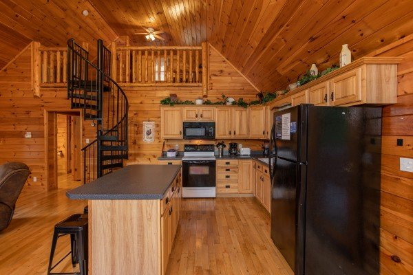Kitchen with black appliances in an open concept room at Can't Bear to Leave, a 1-bedroom cabin rental located in Gatlinburg