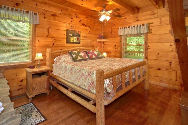 King sized log bed on the main floor at Wild Crush, a 1 bedroom cabin rental located in Pigeon Forge