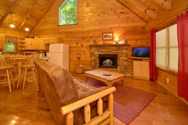 Living room with futon, fireplace, and TV at Wild Crush, a 1 bedroom cabin rental located in Pigeon Forge