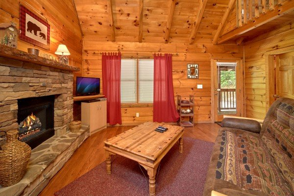 Fireplace and TV in a living room at Wild Crush, a 1 bedroom cabin rental located in Pigeon Forge