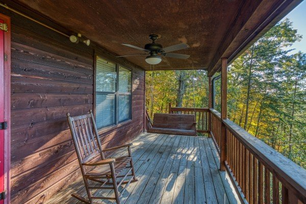 covered porch with a rocker and swing at Apple View, a 2 bedroom cabin rental located in Pigeon Forge