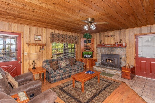 Living room with stone fireplace, couch, and recliners at Apple View, a 2 bedroom cabin rental located in Pigeon Forge