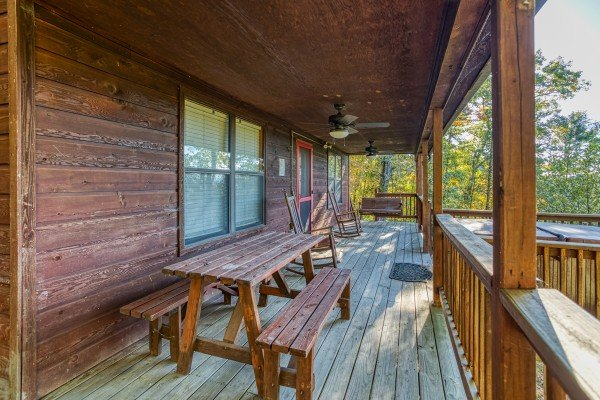 Picnic table on a covered porch at Apple View, a 2 bedroom cabin rental located in Pigeon Forge