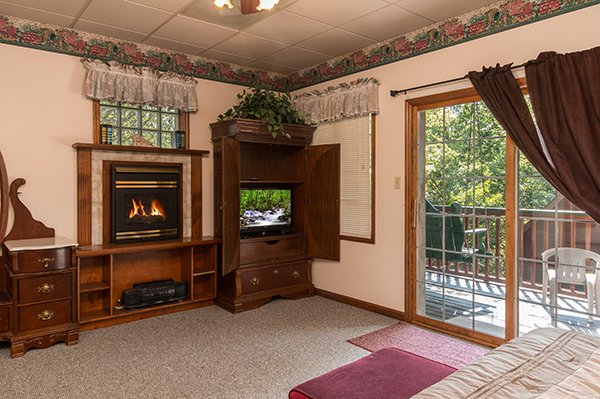Fireplace and television in a bedroom at Ain't Misbehaven, a 1 bedroom cabin rental located in Pigeon Forge