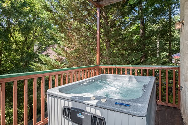 Hot tub on a covered deck at Ain't Misbehaven, a 1 bedroom cabin rental located in Pigeon Forge