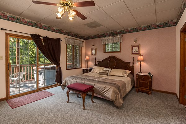 King sized bedroom with deck access at Ain't Misbehaven, a 1 bedroom cabin rental located in Pigeon Forge