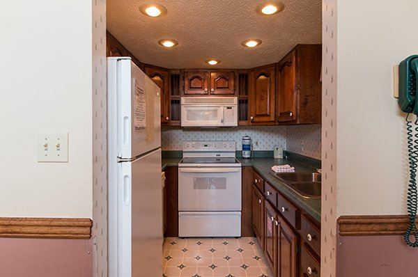 Kitchen with white appliances at Ain't Misbehaven, a 1 bedroom cabin rental located in Pigeon Forge