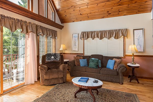 Living room with touch and recliner at Ain't Misbehaven, a 1 bedroom cabin rental located in Pigeon Forge