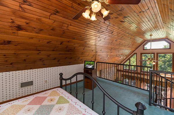 Bedroom with vaulted ceiling open to living space at Ain't Misbehaven, a 1 bedroom cabin rental located in Pigeon Forge