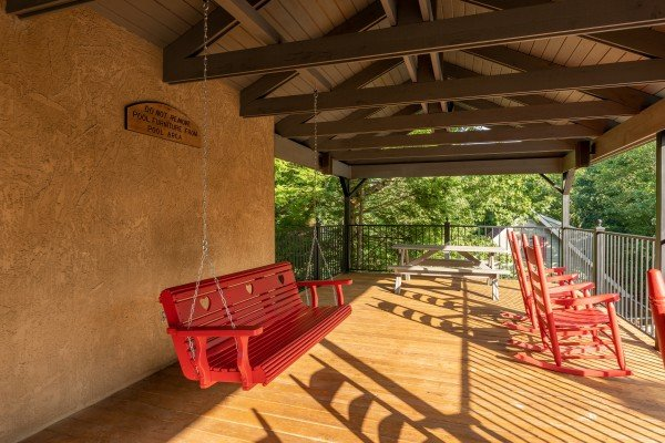 Swing and rocking chairs on a pavilion deck at Ain't Misbehaven, a 1 bedroom cabin rental located in Pigeon Forge