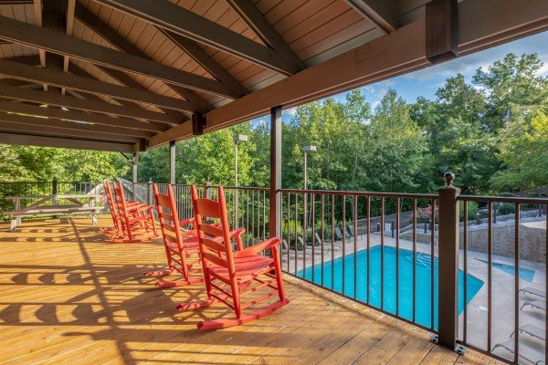 Rocking chairs overlooking the Woodridge Village Resort pool at Ain't Misbehaven, a 1 bedroom cabin rental located in Pigeon Forge