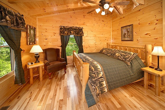 bedroom with king sized bed on a log frame at big bear cub house a 1 bedroom cabin rental located in gatlinburg
