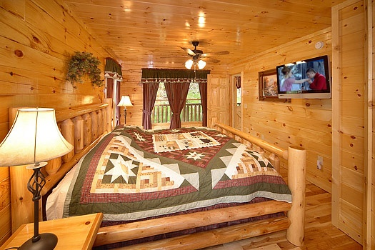 king sized log framed bed in master bedroom at big bear cub house a 1 bedroom cabin rental located in gatlinburg