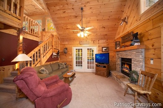 Living room with a fireplace, TV, and deck access Hooked on Bears, a 2 bedroom cabin rental located in Pigeon Forge