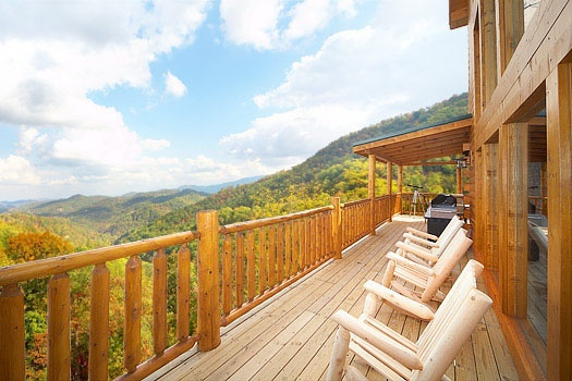 chairs on the deck enjoying the view of the great smoky mountains at don't blink! a 5 bedroom cabin rental located in pigeon forge