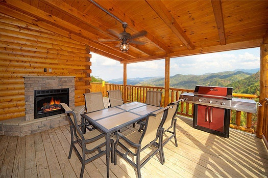 fireplace next to dining table on the deck at don't blink! a 5 bedroom cabin rental located in pigeon forge
