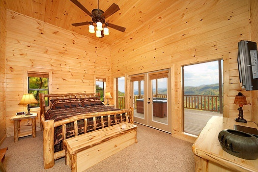 First floor bedroom with king-sized bed and tv above drawers at Don't Blink! A 5-bedroom cabin rental located in Pigeon Forge