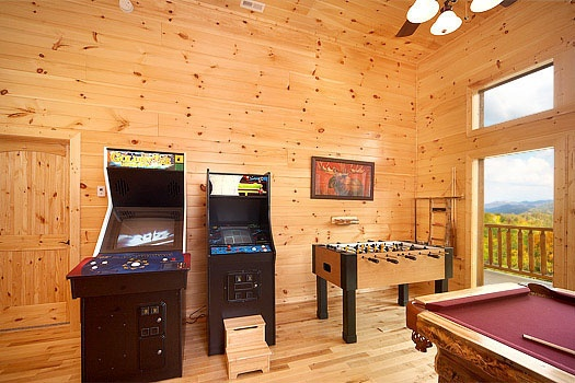 two arcade cabinets and foosball table in game room at don't blink! a 5 bedroom cabin rental located in pigeon forge