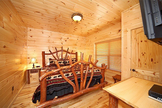 King-sized custom log frame bed at Don't Blink! A 5-bedroom cabin rental located in Pigeon Forge