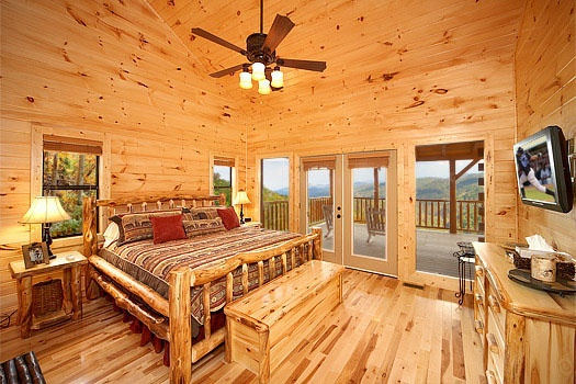 Bedroom with king-sized log framed bed on the main floor at Don't Blink! A 5-bedroom cabin rental located in Pigeon Forge