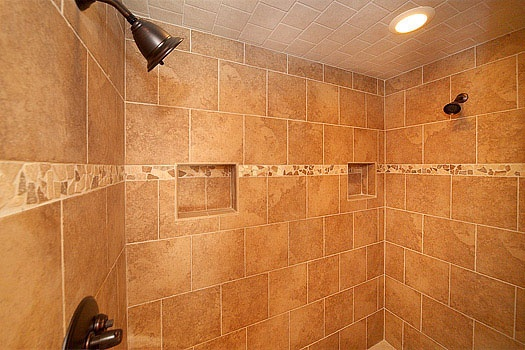 tiled shower with two shower heads in the bathroom at don't blink! a 5 bedroom cabin rental located in pigeon forge