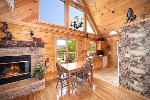 dining table next to fireplace at hooked on cowboys a 2 bedroom cabin rental located in pigeon forge