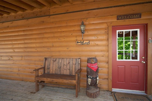 front door with chainsaw art piece of a bear at hooked on cowboys a 2 bedroom cabin rental located in pigeon forge