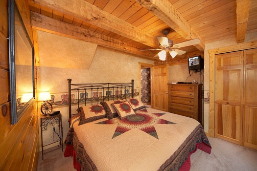 king sized bed in bedroom at hooked on cowboys a 2 bedroom cabin rental located in pigeon forge