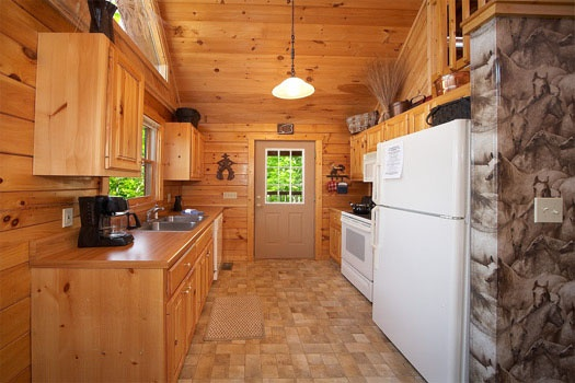 white appliances in the kitchen at hooked on cowboys a 2 bedroom cabin rental located in pigeon forge