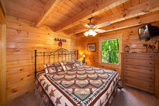 queen sized bed in bedroom at hooked on cowboys a 2 bedroom cabin rental located in pigeon forge