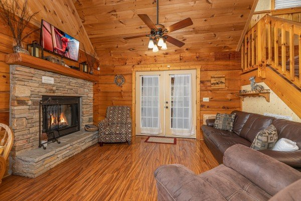 Living room with fireplace and TV at Mickey's Playhouse, a 2 bedroom cabin rental located in Pigeon Forge