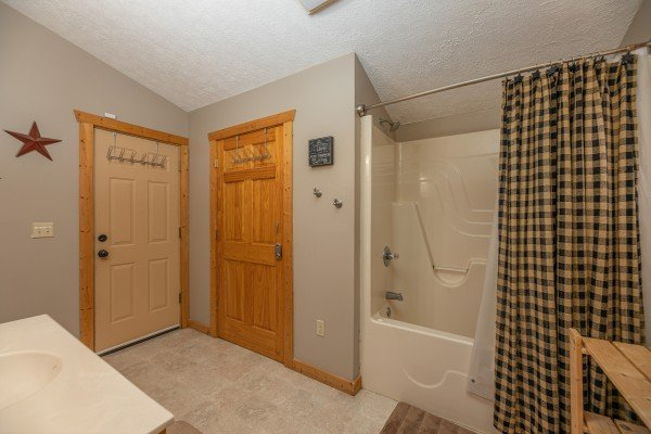 Bathroom with a tub and shower at Mickey's Playhouse, a 2 bedroom cabin rental located in Pigeon Forge