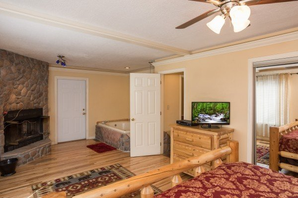 Dresser, fireplace, and jacuzzi in a bedroom at Mountain Laurel, a 1 bedroom cabin rental located in Gatlinburg