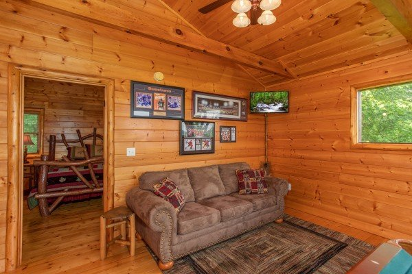 Sofa in the game area at Mountain Adventure, a 2 bedroom cabin rental located in Pigeon Forge