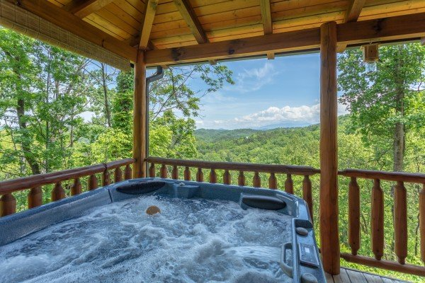 Hot tub views on the covered porch at Mountain Adventure, a 2 bedroom cabin rental located in Pigeon Forge