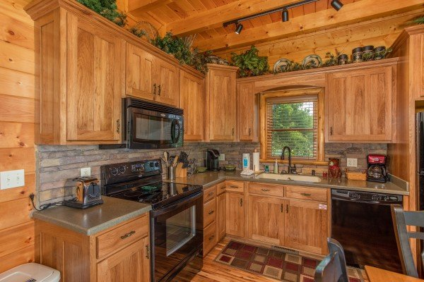 Kitchen with black appliances and stone back splash at Mountain Adventure, a 2 bedroom cabin rental located in Pigeon Forge