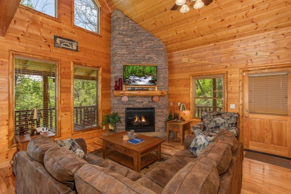 Living room with stone fireplace and TV at Mountain Adventure, a 2 bedroom cabin rental located in Pigeon Forge