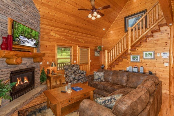 Living room with sectional sofa, fireplace, and TV at Mountain Adventure, a 2 bedroom cabin rental located in Pigeon Forge