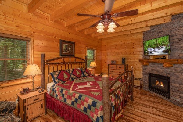 Bedroom with king log bed, dresser, TV, and fireplace at Mountain Adventure, a cabin rental in Pigeon Forge