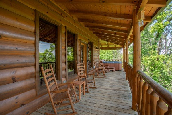 Covered porch with rocking chairs and a hot tub at Mountain Adventure, a 2 bedroom cabin rental located in Pigeon Forge