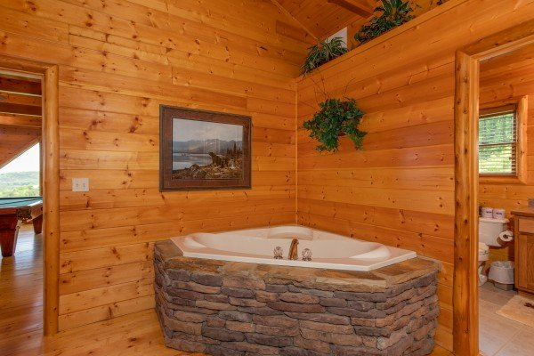 Corner jacuzzi with stone surround at Mountain Adventure, a 2 bedroom cabin rental located in Pigeon Forge