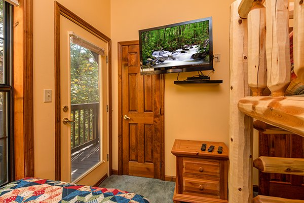 Deck access, TV, and a night stand in the room for three people at Lazy Dayz Lodge, a 4 bedroom cabin rental located in Pigeon Forge