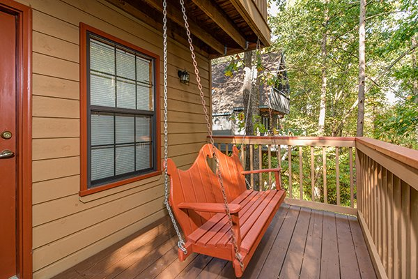 Swing on the porch facing the woods at Lazy Dayz Lodge, a 4 bedroom cabin rental located in Pigeon Forge