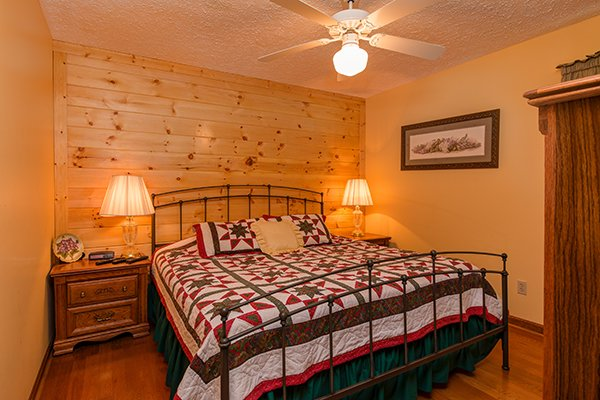Bedroom with a king bed and two night stands at Lazy Dayz Lodge, a 4 bedroom cabin rental located in Pigeon Forge