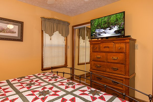Bedroom with a tall chest of drawers and a TV at Lazy Dayz Lodge, a 4 bedroom cabin rental located in Pigeon Forge