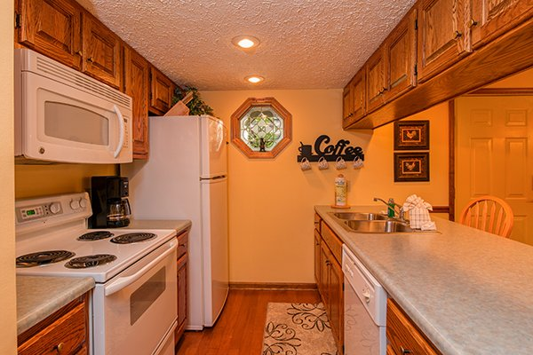 Open galley kitchen with white appliances at Lazy Dayz Lodge, a 4 bedroom cabin rental located in Pigeon Forge