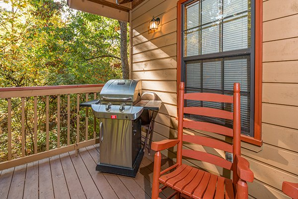 Rocking chair and gas grill on the covered porch at Lazy Dayz Lodge, a 4 bedroom cabin rental located in Pigeon Forge