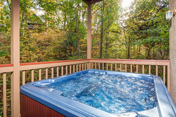 Hot tub on a covered deck surrounded by woods at Lazy Dayz Lodge, a 4 bedroom cabin rental located in Pigeon Forge