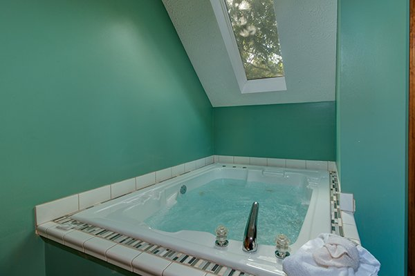Jacuzzi tub under a skylight at Lazy Dayz Lodge, a 4 bedroom cabin rental located in Pigeon Forge